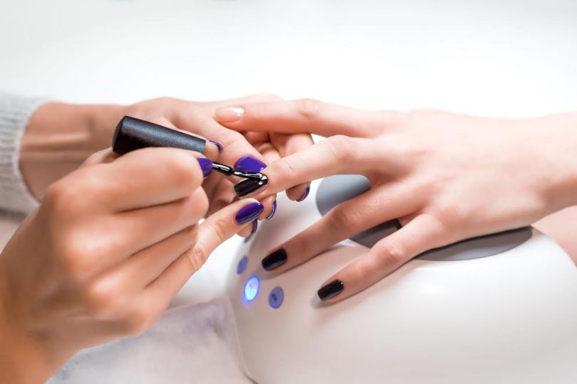 48554974 - closeup manicurist applies nail gel polish on middle finger. girl client holds hand on the client on uv lamp. beautician gently manicured service.