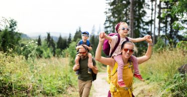 Family,With,Small,Children,Hiking,Outdoors,In,Summer,Nature.
